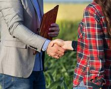 banker and farmer shaking hands in field