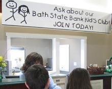 banner promoting kids club in bank lobby