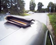 forgotten wallet on top of car driving on road