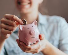 lady putting coin in pink piggy bank
