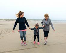 grandmother, mother and child on a beach